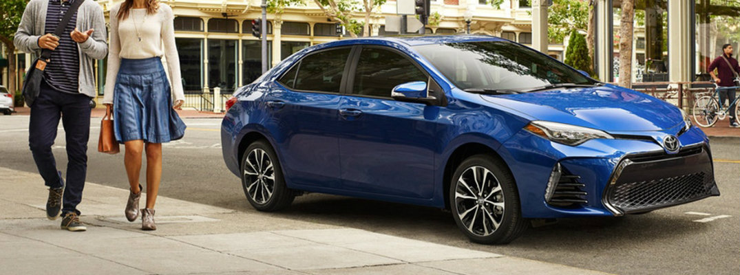 Exterior view of a blue 2019 Toyota Corolla parked curbside in the city with a man and woman walking nearby