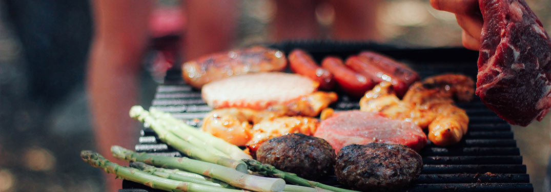 Burgers, brats and asparagus on a grill