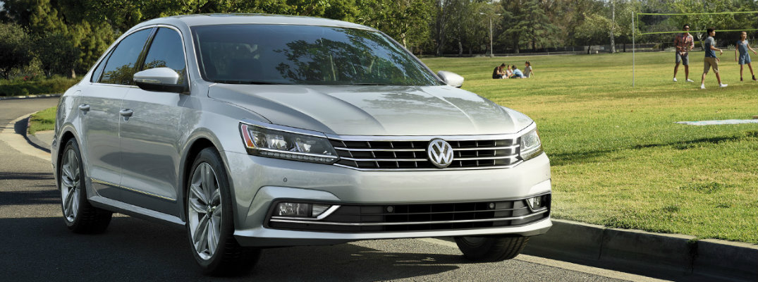 Silver 2018 Volkswagen Passat driving through park with people looking at it