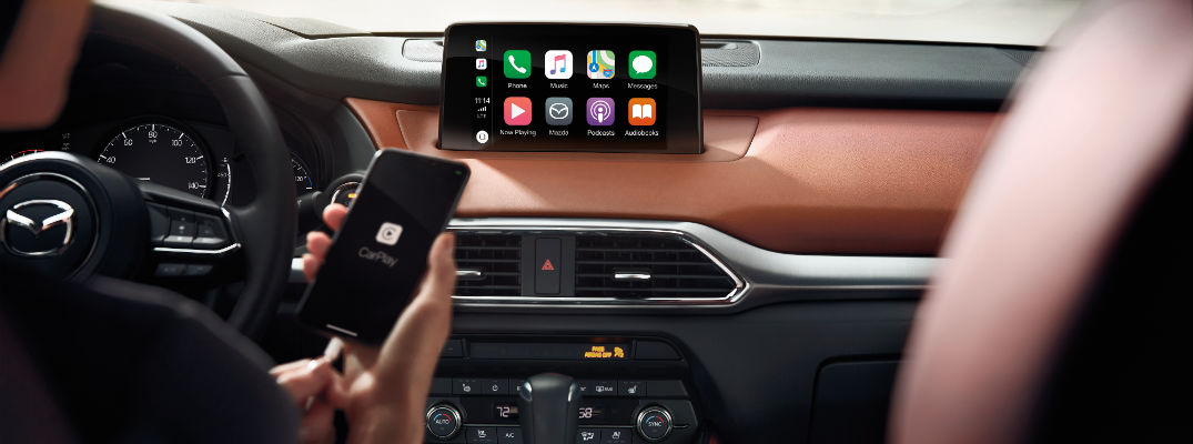 A photo of someone plugging their smartphone into a Mazda infotainment system.
