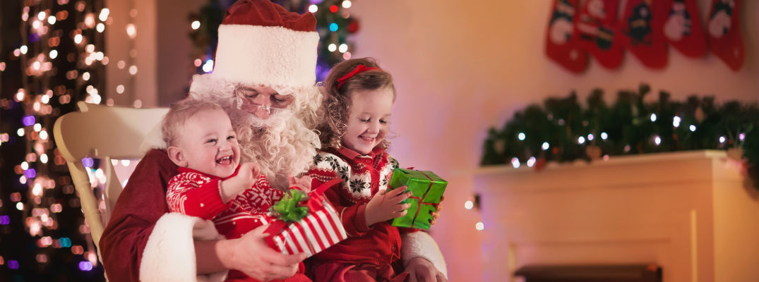 A stock photo of children sitting on Santa's lap.