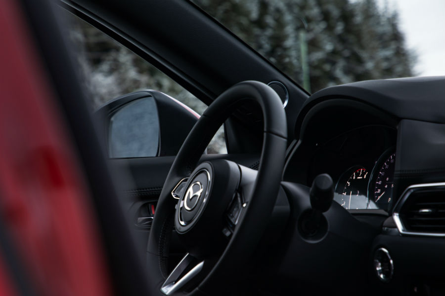 A photo of the steering wheel and parts of the driver's cockpit in the 2019 Mazda CX-5.