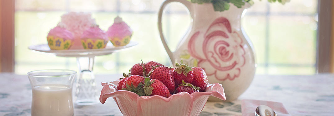 China pitcher with a pink rose by a pink flowery bowl filled with strawberries