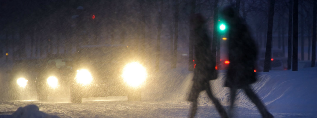 2 people crossing the road through snow in front of a line of cars with their lights on
