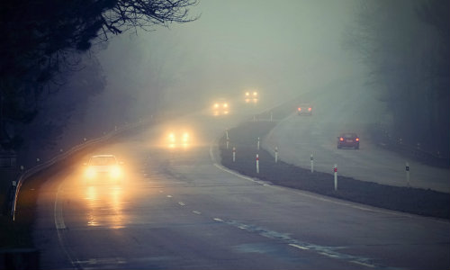 foggy and rainy road with car driving with headlights on