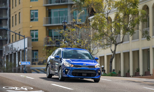 2018 Kia Rio blue driving on a street in a city in the day sunlight