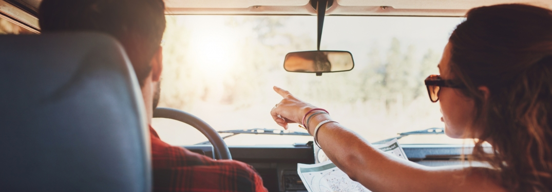 Man and woman on a road trip with a map