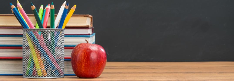 school books an apple pencils and a blackboard
