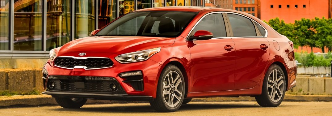 2019 Kia Forte red side view in front of a glass building
