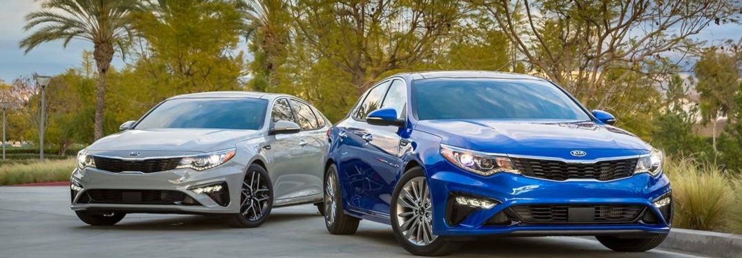 2020 Kia Optima blue and white in front of palm trees