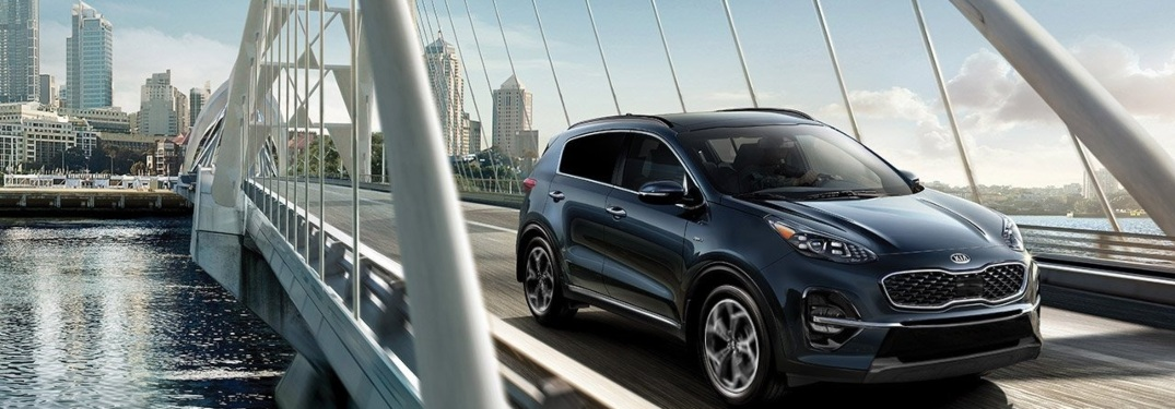 2020 Kia Sportage driving on bridge with cool city in background