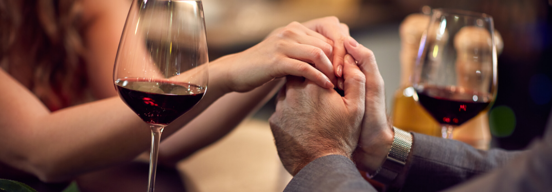 Couple holding hands with wine nearby