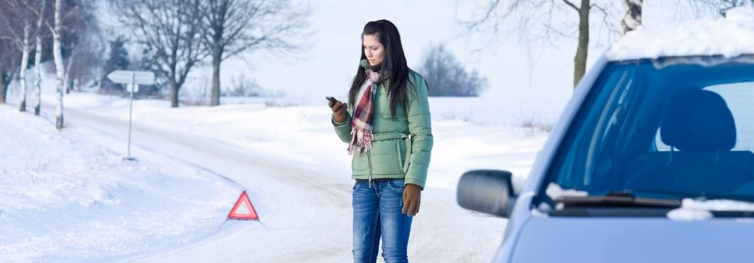Woman calling for help on the side of a snowy road silver car in the foreground warning marker in the background