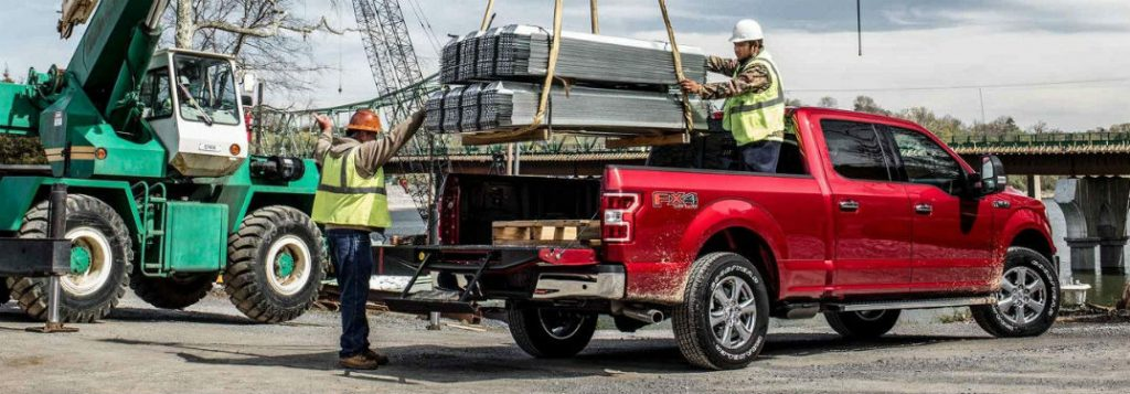 two construction workers loading the bed of a 2018 ford f-150
