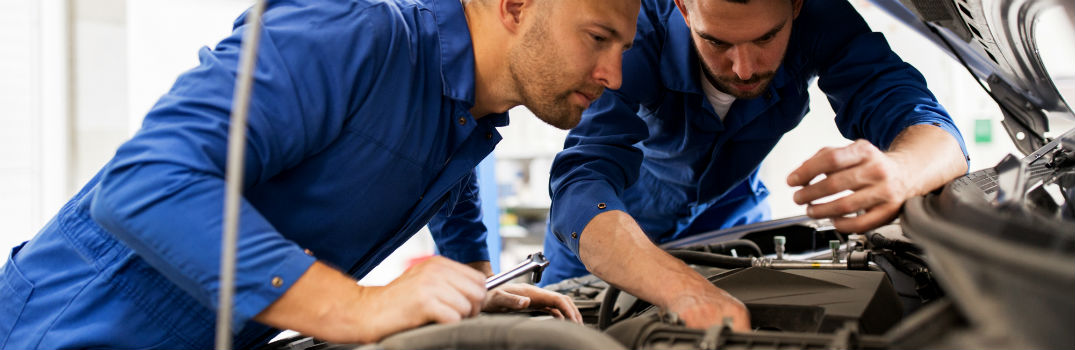 two service technicians under the hood of a vehicle