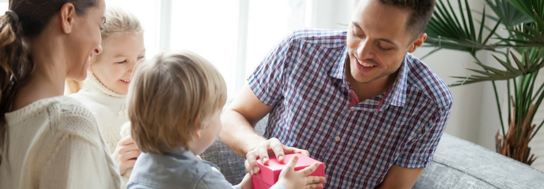 father receiving gifts from small child with wife