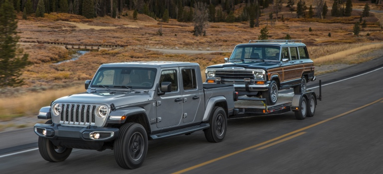 2020 Jeep Gladiator silver towing a classic Jeep on a ...