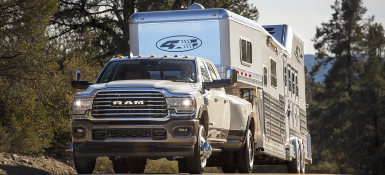 2019 RAM 3500 white towing a large white trailer front view