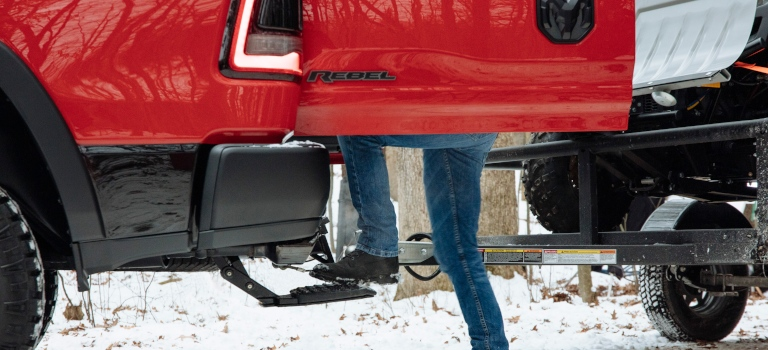 2019 RAM 1500 Rebel in red with a multi-function tailgate and a center step