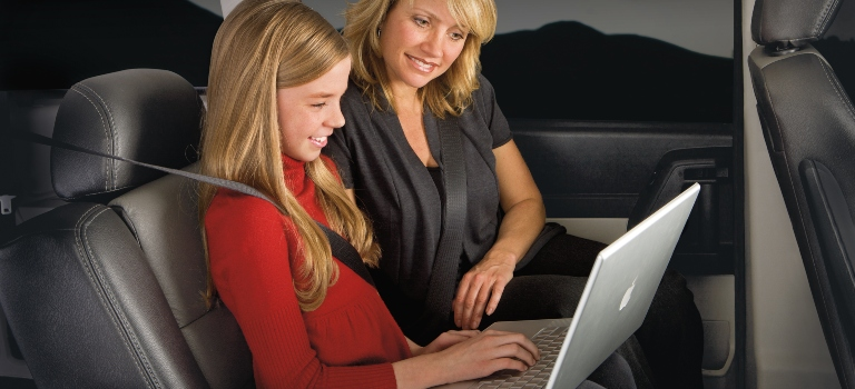 Girl using a laptop in a FCA car