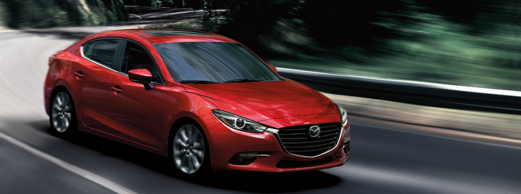 2018 Mazda3 soul red metallic paint color driving through giant clifss and tree in a jungle highway
