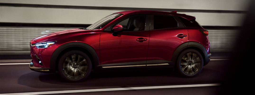 2019 Mazda CX-3 red compact SUV new york international aut show exterior side shot driving through a tunnel