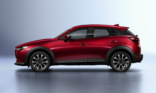 2019 Mazda CX-3 exterior shot soul red compact SUV parked in a blank showroom