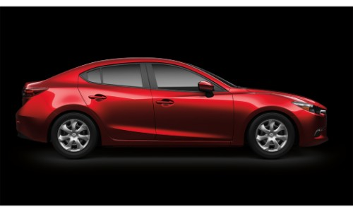 2018 Mazda3 sedan exterior side shot red in a black showroom