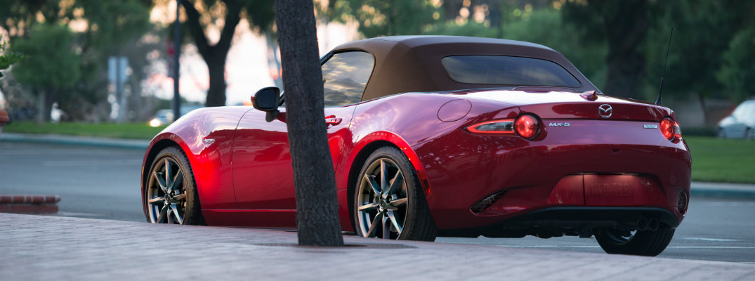 2019 Mazda MX-5 Miata exterior shot with red paint and a brown softop parked outside a building behind a tree