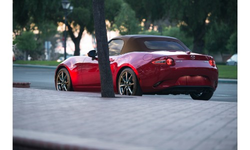 2019 Mazda MX-5 Miata exterior shot soft top red paint job parked outside a building