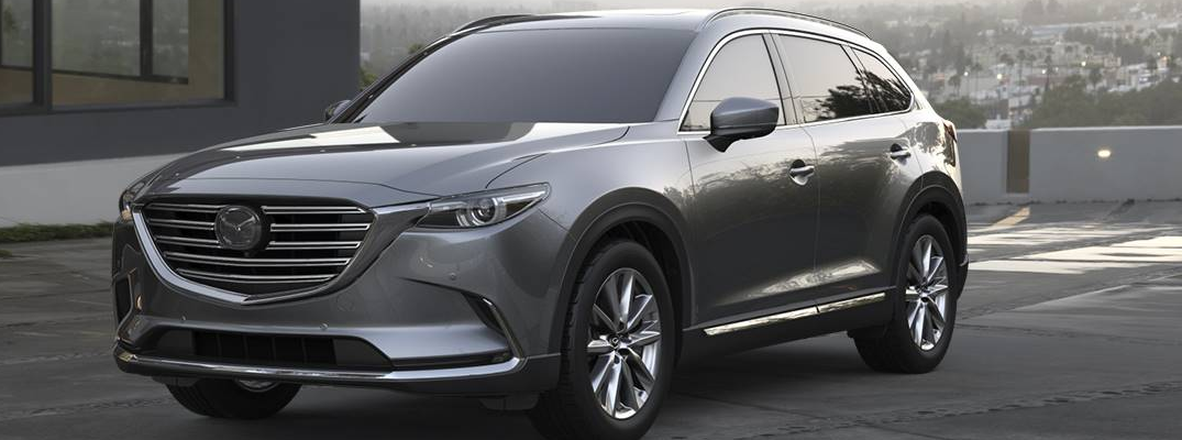 2019 Mazda CX-9 exterior shot with gray silver paint job parked next to a house with a california neighborhood in the background at dusk