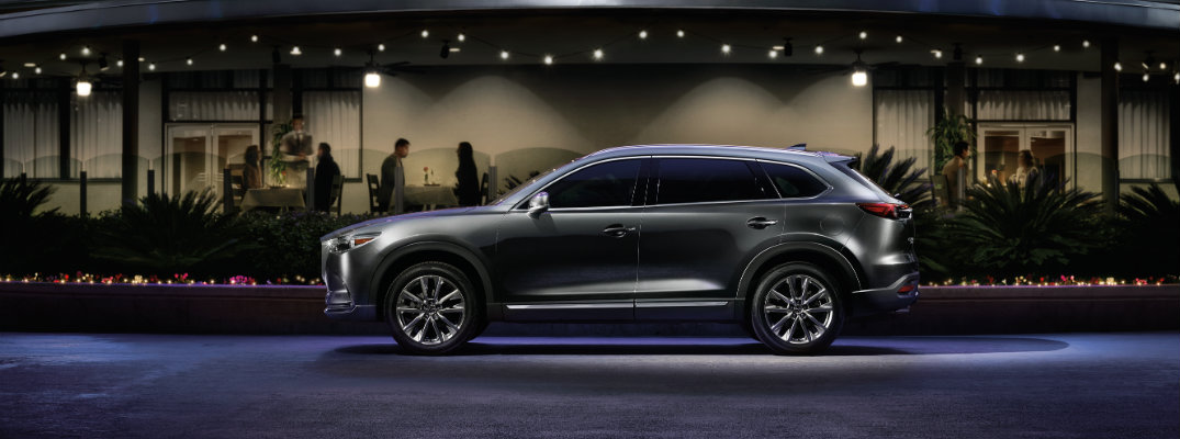 2019 Mazda CX-9 exterior side shot parked outside a luxury restaurant outside the neon purple light of the title sign