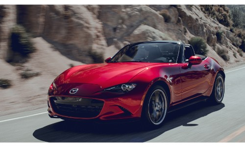 2019 Mazda MX-5 Miata exterior shot with red paint color driving down a desert road near a rocky cliff