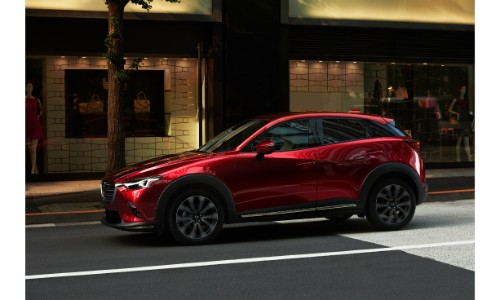2019 Mazda CX-3 exterior side shot with red paint color driving in a city and passing a quaint cafe