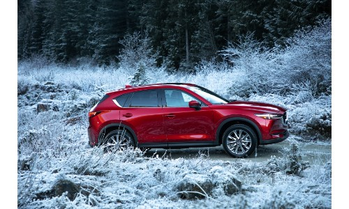 2019 Mazda CX-5 exterior side shot with red paint color driving off-road in a wild and snowy forest