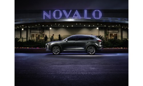 2019 Mazda CX-9 exterior side shot with gray metallic paint color parked under the purple lighting of a large sign