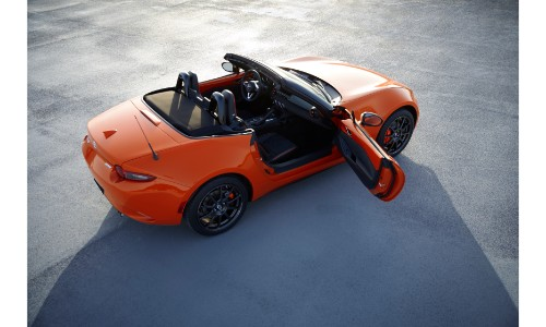 2019 Mazda MX-5 Miata 30th Anniversary Edition exterior overhead with racing orange paint color, door open, and shadow cast