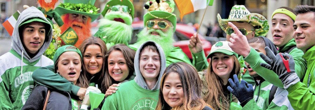 A group of people celebrating St. Patrick's Day in March at an event outside.