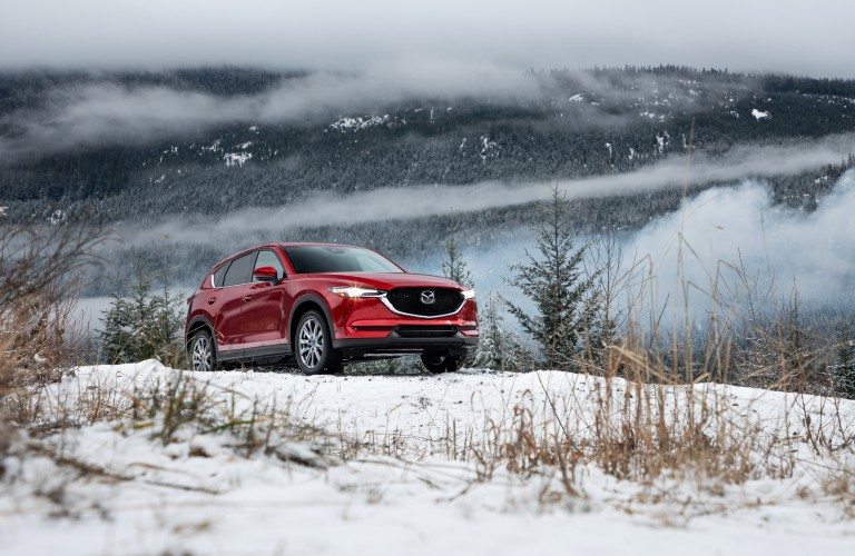 A 2020 Mazda CX-5 driving over a snowy hill in the middle of winter.