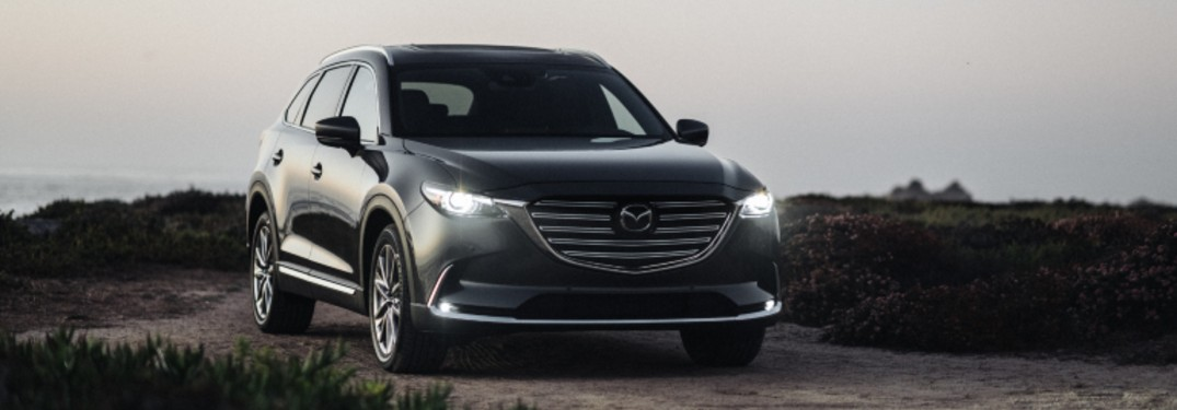 A black 2020 Mazda CX-9 Signature trim with its lights on while parked on a hill at dusk.